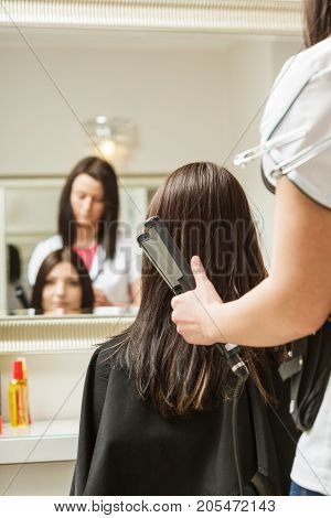Haircare wellness concept. Woman getting her hairstyle done at hairdresser salon modeling hair using straightener