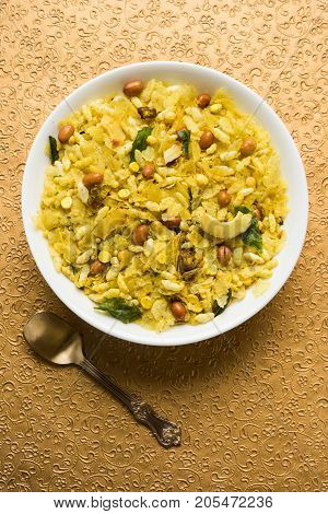 Indian traditional and popular snack poha chivda or chivada made from frying items like thin flattened rice, red chili, curry leaves, groundnuts, cashew nuts and almonds. selective focus