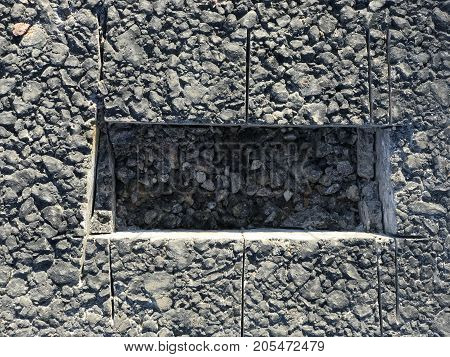 Place of sampling the asphalt coating in the form of a rectangular from asphalt concrete pavement. Kern. Close-up