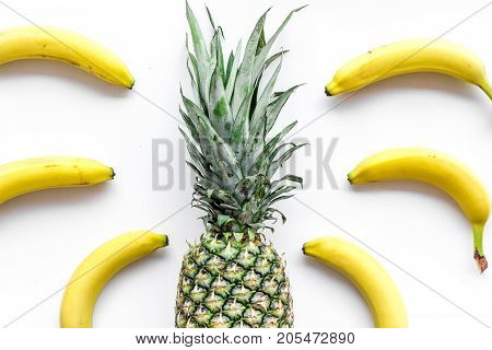 Tropical fruits pattern. Pineapple and bananas on white background top view.