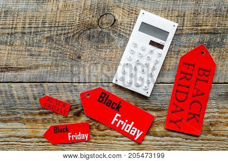 Words black friday on colored labels and calculator on wooden background top view.