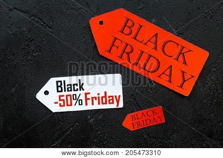 Words black friday on colored labels on black background top view.