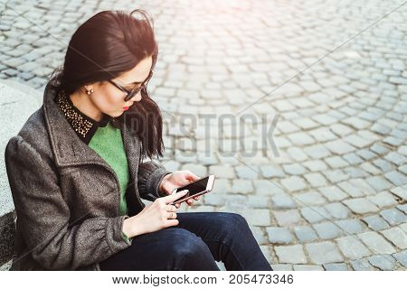 Brunette Girl Sitting On The Street With Cellphone