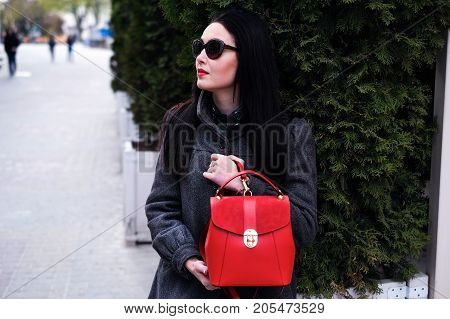 Woman Sitting On The Street With Red Backpack
