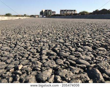 Rough asphalt pavement in the summer season. Close-up