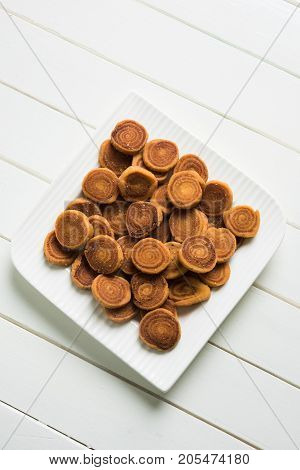 Stock Photo of Indian Fried Bhakarwadi Tea Time Snack also known as bakarwadi, bakarvadi, bakar vadi, bakar wadi or spring roll is a traditional spicy Maharashtran and Gujarat Snack poster