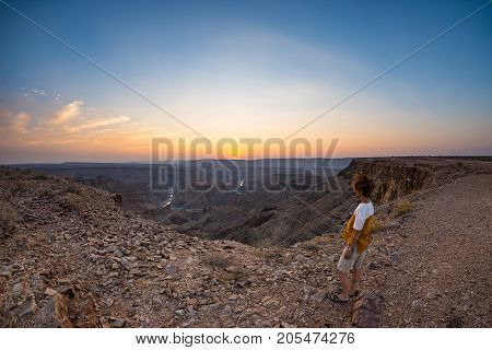 Tourist Looking At The Fish River Canyon, Scenic Travel Destination In Southern Namibia. Ultra Wide