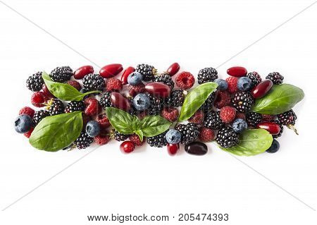 Black-blue and red berries isolated on white. Ripe blackberries blueberries raspberries cornels and basil leaves on white background. Berries with copy space for text. Top view.