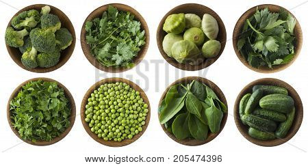Top view. Green vegetables and herbs isolated on a white background. Squash brocoli green peas cucumbers and leaves parsley celery cilantro spinach in wooden bowl with copy space for text.