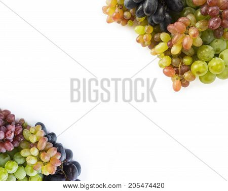 Grapes on white background. Grapes with copy space for text. Top view. Blue red and green grapes. Vegetarian or healthy eating.