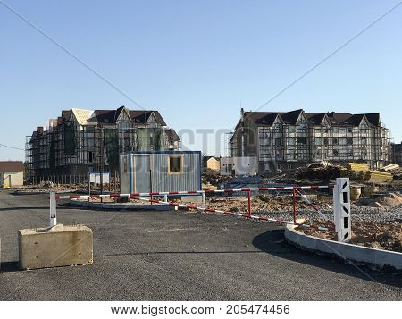 Gate to restrict entrance to the construction site. Construction of multi-storey apartment buildings in the summer