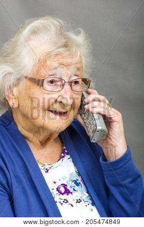 Senior Citizen using a Telephone. Senior lady talking on a cordless telephone