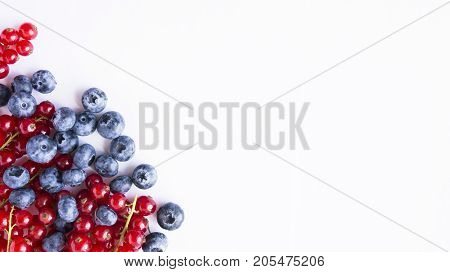 Ripe blueberries and red currants. Red and blue berries. Berries at border of image with copy space for text. Background berries. Top view. Various fresh summer berries on white background.