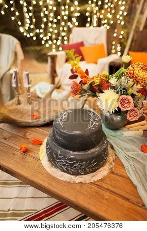wedding, treatment, cooking concept. composition made of delicious cake of unique for food black colour, bunch of charming flowers, candles and twinkle light on the background