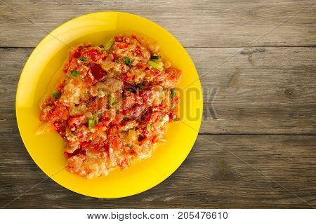 Stewed Tomatoes With Onions In A Plate On A Wooden