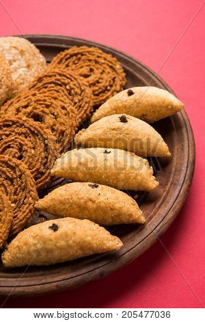 stock photo of Indian festival or diwali food called chakli, anarsa and karanji or Gujiya, selective focus