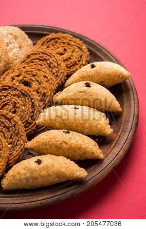 stock photo of Indian festival or diwali food called chakli, anarsa and karanji or Gujiya, selective focus