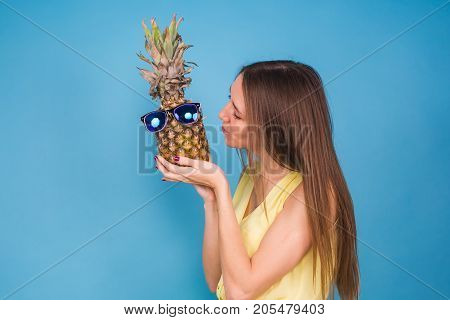 Happy young woman holding a pineapple with sunglasses on a blue background. Vacation, summer, vegetarians and detox concept.