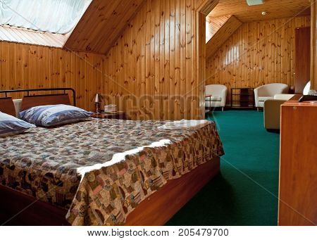The interior of a room with a loft, decorated in wooden style