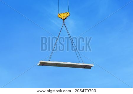 Concrete slab hanging on the cables of the crane hook