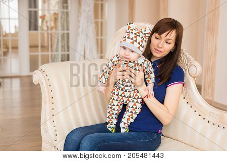 Loving Mother Holding Baby Son At Home