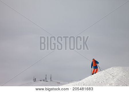 Skier Before Downhill On Freeride Slope And Misty Sky