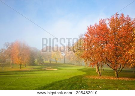 Morning mist and sun light. Fog over golf course during beautiful fall sunrise. Colorful autumn trees on a bright green lawn. Horizontal composition.