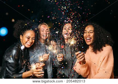 Happy friends. Group of smiling women holding sparklers under confetti