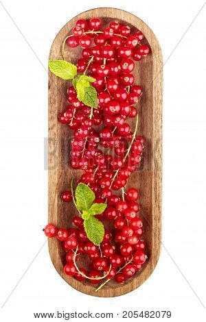 Ripe redcurrants on wooden plate isolated on a white background. Top view