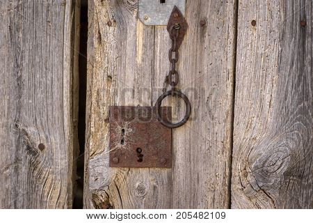 Closeup vintage door lock of external antique wooden door weathered on a Country house