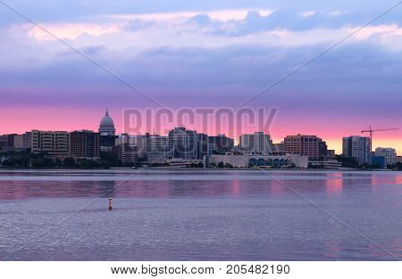 Downtown skyline of Madison the capital city of Wisconsin USA.After sunset view with State Capitol building dome against beautiful colored sky as seen across lake Monona.