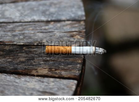 Burning cigarette with ash and smoke left on the outdoor wooden table. Bad habit concept background.