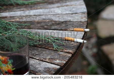 Burning cigarette with ash and smoke in focus left on the outdoor wooden table next to almost empty glass with wine and another cigarette stub out of focus. Bad habits concept background.