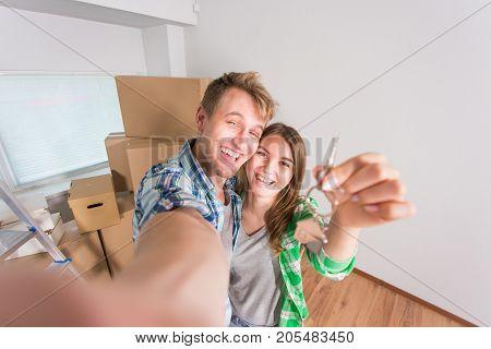 Happy couple showing keys of new home indoor