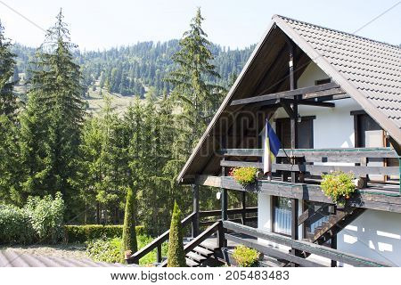 Mountain wooden hut and villas on a hill with fresh green mountain pastures trees in the background.