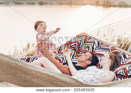 Young Family With Baby On The Beach, Smiling Father And Mother Holding Cute Little Girl While Lying