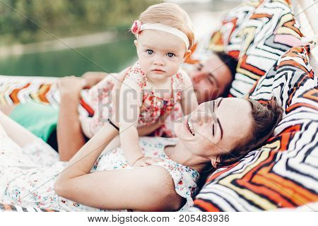 Happy Young Mother Holding Baby Daughter In Hands While Relaxing In Hammock With Husband, Hipster Fa