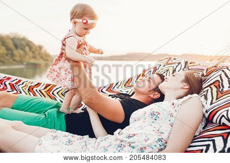 Strong Young Father Holding His Baby Daughter In Hands With Happy Hipster Mother, Smiling Family Rel