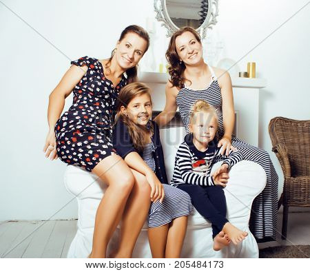 young pretty modern family at home happy smiling, lifestyle people concept, mother with cute little daughter, sister twins together close up