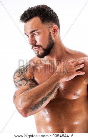 Male fitness model posing shirtless over white background. Portrait of Young beautiful sexy man with tattooed torso.