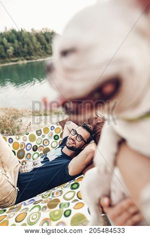 Happy Woman Holding Cute Bulldog With His Tongue Out, Husband On A Hammock In The Background, Hipste