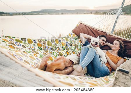 Hipster Family On Vacation Concept, Happy Woman And Man Relaxing On A Hammock At The Beach With Thei