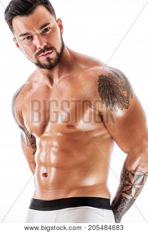 Young man with beautiful tattooed torso posing in underwear. Muscular sexy fitness model sitting shirtless and looking at the camera.