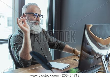 Full of inspiration. Positive elderly bearded man in glasses is sitting at table and looking for information on computer while writing historical novel