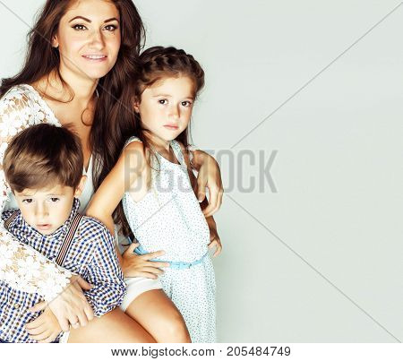 young mother with two children on white background, happy smiling family inside isolated close up