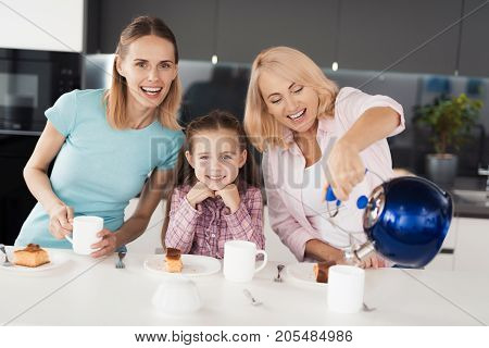A girl, her mother and her grandmother are posing in the kitchen for tea. Before them a homemade cake on plates, the grandmother pours water from the cup into the kettle