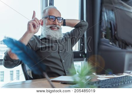 Great idea. Cheerful bearded senior writer in glasses is sitting at table and expressing gladness while looking at screen of computer and pointing up
