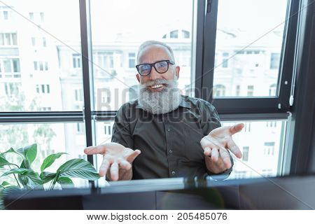 What else. Cheerful old bearded man is sitting at table against window and working on computer. He is gesticulating while looking at camera with joy