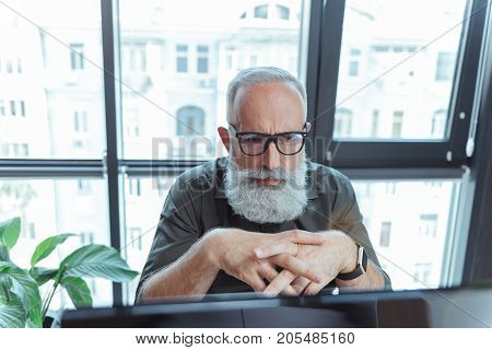 Heavy thoughts. Portrait of serious bearded senior author is leaning on table and looking forward thoughtfully. Man in glasses is sitting with computer against window