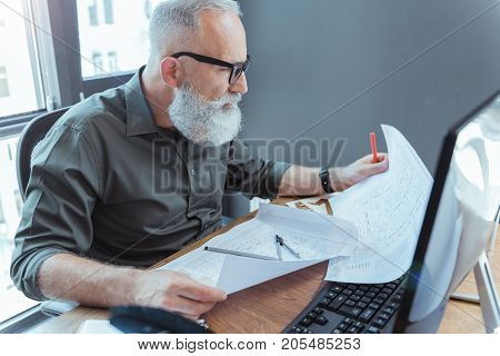 Involved in job. Profile of bearded mature man in glasses is sitting at table against window and laboring with concentration. He is holding his project and thinking hard